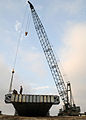 US Navy 080709-N-1424C-453 An elevated causeway structural support part is being lowered into place.jpg