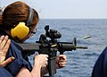 US Navy 080725-N-4236E-391 Fire Controlman Seaman Rachel Hubley fires an M4 carbine from the fantail of the guided-missile cruiser USS Vella Gulf (CG 72).jpg