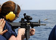 US Navy 080725-N-4236E-391 Fire Controlman Seaman Rachel Hubley fires an M4 carbine from the fantail of the guided-missile cruiser USS Vella Gulf (CG 72)