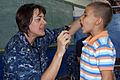 US Navy 090628-F-7885G-125 Lt. Cmdr. Kelly Hamon, embarked aboard the Military Sealift Command hospital ship USNS Comfort (T-AH 20), examines a young boy during a Continuing Promise 2009 medical community service project.jpg