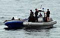 US Navy 100331-N-7058E-720 A response team of Sailors and Coast Guardsmen from the littoral combat ship USS Freedom (LCS 1) question four suspected drug smugglers after their.jpg