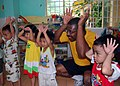 US Navy 100812-N-8539M-120 Cryptologic Technician 1st Class Cody Perez sings along with children at a Da Nang primary school during a community service project.jpg