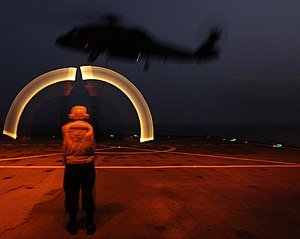 Aircraft marshalling - A long exposure of a United States Navy Landing Signalman Enlisted (LSE) directing a SH-60F Sea Hawk to take off using marshalling wands