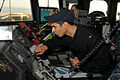 US Navy 110609-N-NL541-122 Ensign Angel Cruzcruz cranks the growler of the sound-powered phone on the ship's bridge while making a contact report t.jpg