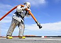 US Navy 110927-N-WJ771-108 Aviation Support Equipment Technician 2nd Class Joshua B. Cary carries a charged hose across the flight deck of USS Denv.jpg