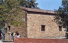 Photo of a building of rough stone with small windows, surrounded by olive trees