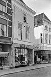 foto van Hoekpand met geverfde gevel met kroonlijst en jongere winkelpui