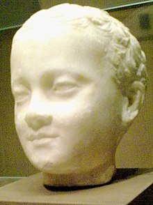 Three-quarter view of a sculpture of a young child's head, the child appears smiling his face has relaxed expressions as he gazes over the viewer's shoulders