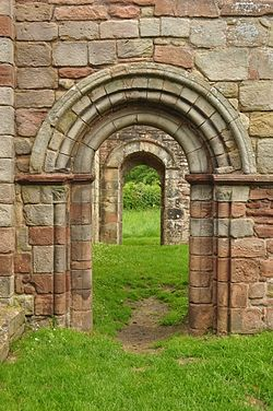 A photograph showing a round arch in a wall, with a similar arch beyond seen through it.