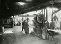Woman acting as helper at punching and shearing machine (15402564842).jpg