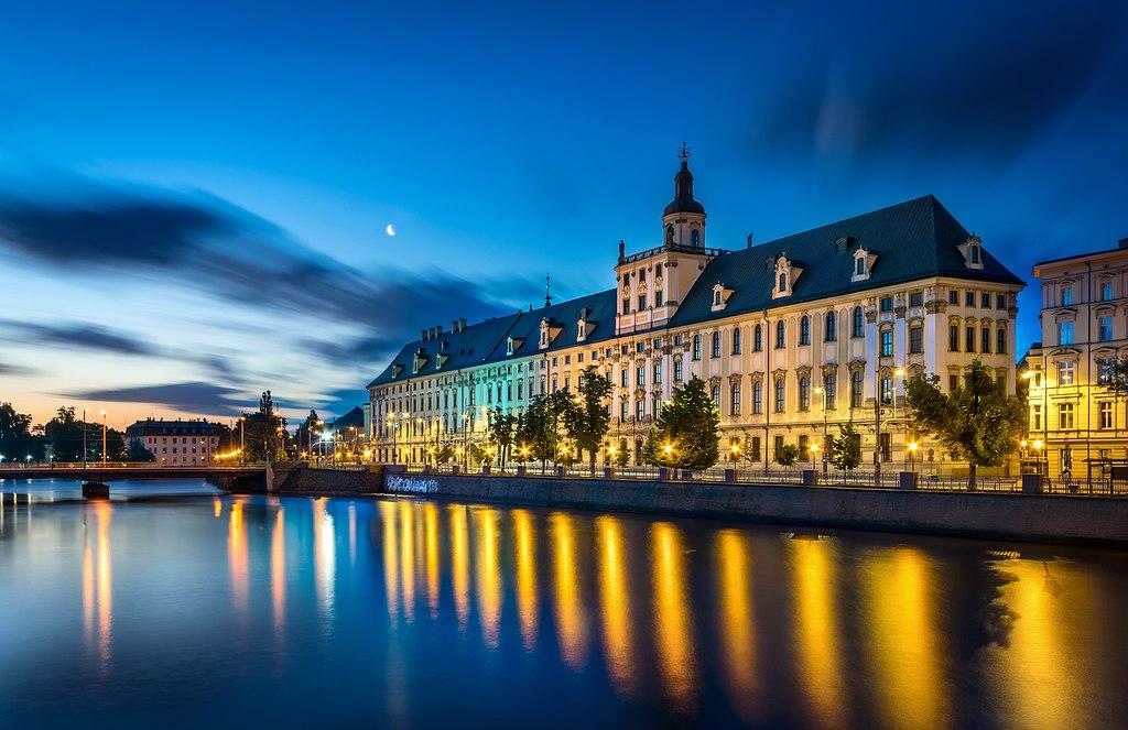 Université de Wroclaw au bord de l'eau avec la tour mathématiques dépassant du toit. Photo de Jar.ciurus.