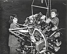 Two Marine Corps women reparing an airplane engine