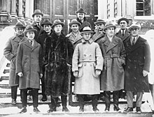 Twelve men pose on the steps in front of a building. They are wearing suits, long jackets and hats.