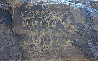 History of Niger - Ancient rock engraving showing herds of giraffe, ibex, and other animals in the southern Sahara near Tiguidit, Niger.