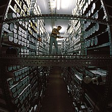 A man on a walkway between two high shelf racks loaded with ice core samples