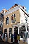 foto van Huis met gepleisterde lijstgevel. Dakkapel. Piron. Zijgevel met uitbouw oorspronkelijk pothuis, aan de zijde van de Lepelstraat. Winkelpui