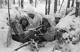A group of Finnish soldiers in snowsuits manning a heavy machine gun in a foxhole.