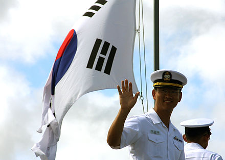 A South Korean navy petty officer aboard ROKS Munmu the Great (DDH 976) waves to onlookers pier side. A South Korean navy petty officer.jpg