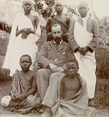 Black and white photo of a seated man wearing a suit suit, surrounded by several young Ugandan men.