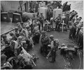 American soldiers, hardened and ready, lounge under full fighting equipment on the deck of a Coast Guard assault... - NARA - 196237.tif