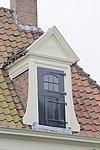 Woonhuis, pilastergevel met rechte kroonlijst en hoog tentdak, door drie schoorstenen versierd. Dakvensters door tympanen bekroond. Vormt een geheel met nr 13