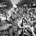 An AFPU photographer kisses a small child before cheering crowds in Paris, 26 August 1944. BU18.jpg