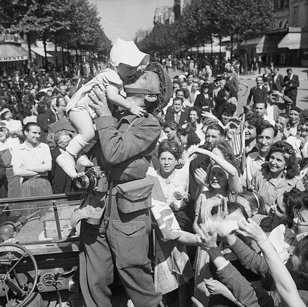 An American photographer hoists and kisses a child in front of a crowd, Paris, 1944