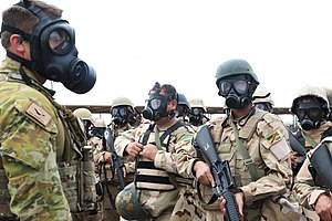 An Australian soldier with Task Group Taji inspects Iraqi soldiers during CRBN training