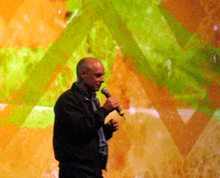 A bald man speaking into a microphone is standing in front of an abstract painting containing blotches of orange and lime green and corrugated lines.