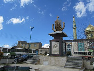 Benis - Statue in village square of Benis. The mosque can be seen in the background.