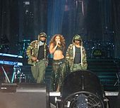 Two men and a woman are looking forward. Both men are wearing military-style clothing, while the woman is holding a microphone. She wears gypsy-style clothing. In the background, many musical instruments are visible.