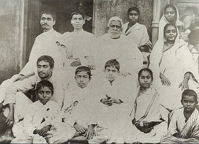 A group photograph of a large Indian family seated in rows around an old grey-haired man.