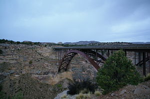 A dusk picture of a steel arch bridge spanning a deep canyon. In the background the corner of a 2nd bridge is visible.