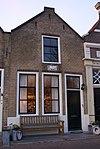 foto van Huis met puntgevel met schuiframen en stoep