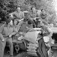 Three soldiers sit on a tank while two more stand next to it.
