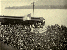 A dramatic political scene. Beside a river stands a podium, on which a flagpole flies a huge American flag. Beneath the flag stands a candidate in a dark suit addressing an impressive crowd that takes up most of the photograph. Not only the quayside, but a ferry beside it on the water are packed full of people listening intently.
