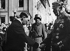 Photo noir et blanc sur laquelle le chancelier Hitler en civil s'incline devant le président Paul von Hindenburg, en uniforme de maréchal, pour la journée de Potsdam, le début de la session parlementaire au Reichstag noiuvellement élu.