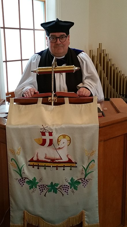 An Anglican minister delivers a homily, dressed in choir habit with Canterbury cap Canterbury Cap.jpg