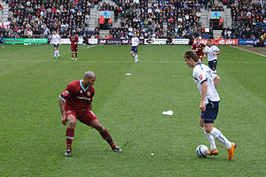 A striker in a white and navy blue soccer strip has the ball. The defender, wearing a claret strip, attempts to make the tackle.
