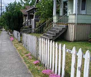 Picket fence domestic boundary of evenly spaced vertical boards attached to a horizontal rail