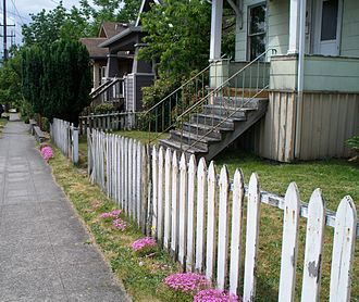 Picket fence - Classic picket fence next to a sidewalk.
