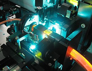 Dye laser - Close-up of a table-top CW dye laser based on rhodamine 6G, emitting at 580 nm (yellow). The emitted laser beam is visible as faint yellow lines between the yellow window (center) and the yellow optics (upper-right), where it reflects down across the image to an unseen mirror, and back into the dye jet from the lower left corner. The orange dye-solution enters the laser from the left and exits to the right, still glowing from triplet phosphorescence, and is pumped by a 514 nm (blue-green) beam from an argon laser. The pump laser can be seen entering the dye jet, beneath the yellow window.