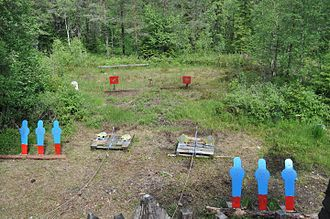 Cowboy action shooting - Steel targets down range at the stage. The shooter engages the targets with different weapons, using a rifle for the distant red targets, and revolvers for the closer blue targets.