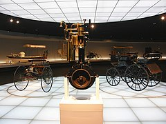 Daimler-Maybach grandfather clock engine and early carriafges at Mercedes Museum.jpg