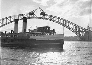 The Dee Why ferry passes the unfinished Sydney Harbour Bridge