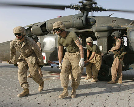 Marines unload a wounded comrade from an Army UH-60 Blackhawk helicopter for medical treatment at Al Qaim. Defense.gov News Photo 051107-M-5865P-021.jpg
