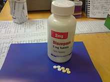 White bottle with red and black labels on a blue pad atop a desk. Also on the pad are seven small pills.