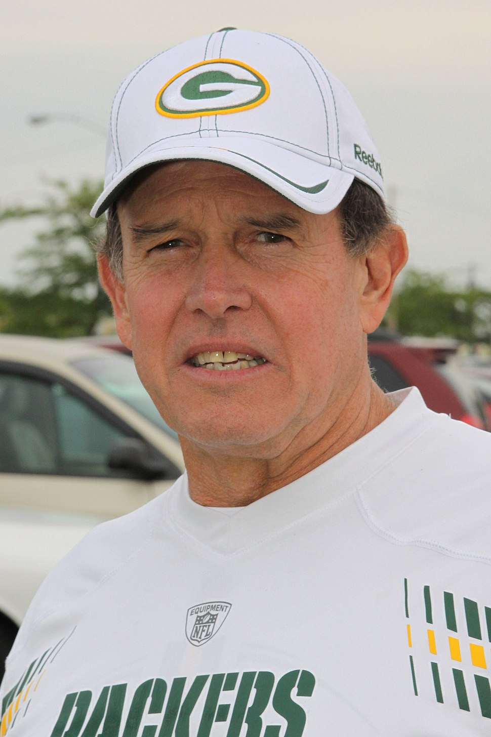 Head and shoulders photograph of Capers wearing a white Green Bay Packers t-shirt and white Packers baseball cap