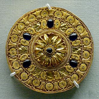 Etruscan jewelry - Ear-stud decorated with a rosette surrounded by concentric bands. Gold with vitreous glass paste insets, 530–480 BC. British Museum.