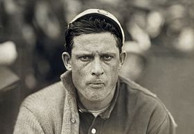 "A man in a baseball jersey and a white sweater, which is worn over only his right sleeve. The man is also wearing a light-colored baseball cap with a ""C"" on the front. His face is freckled, and his eyes look directly into the camera."